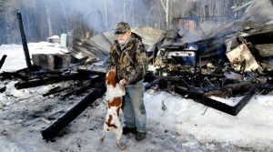 Homeowner Herb Hingley's dog Babe jumps up on him beside his home that was destroyed by fire on the Rowe Pond Road in Pleasant Ridge on Wednesday. Hingley credited his dog with jumping on him and alerting him to the early morning fire. Staff photo by David Leaming